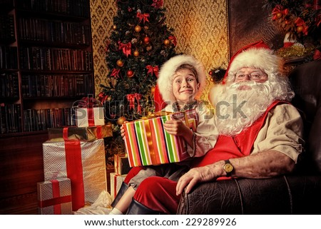 Happy little boy sitting on the lap of Santa Claus and rejoice a gift. Christmas decoration.  - stock photo