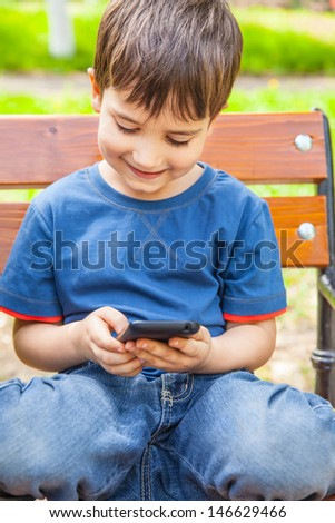 Happy little boy smiling and playing with smartphone - stock photo