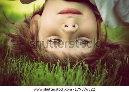Happy little boy standing upside down on green grass in spring park, instagram effect - stock photo