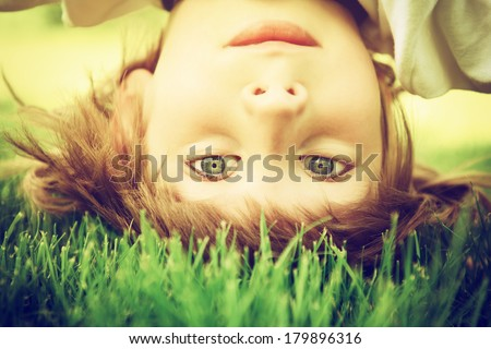 Happy little boy standing upside down on green grass in spring park, intstagram effect - stock photo
