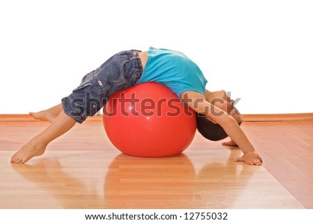 Happy little boy stretching on a gymnastic ball - isolated - stock photo