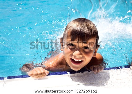 happy little boy swimming in the pool