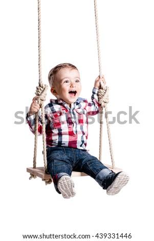 happy little boy swinging on a wooden swing - stock photo