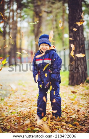 Happy little boy throws the autumn leaves in the air. - stock photo