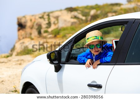 happy little boy travel by car in summer mountains