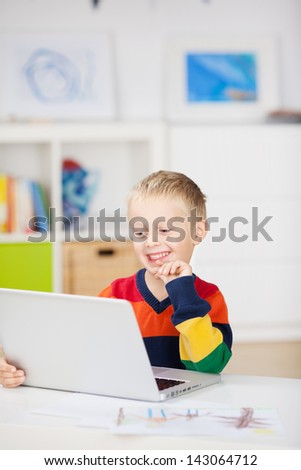 Happy little boy using laptop at table in house