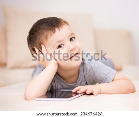 Happy little boy using tablet - stock photo