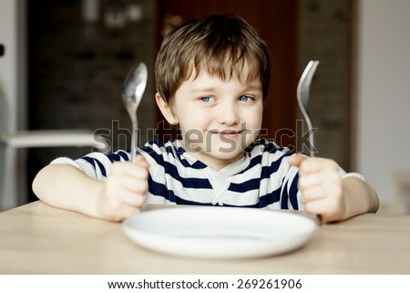Happy little boy waiting for dinner. Holding a spoon and fork in the hand