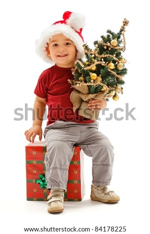 Happy little boy wearing Santa hat, sitting on big present box and holding small, decorated Christmas tree - stock photo