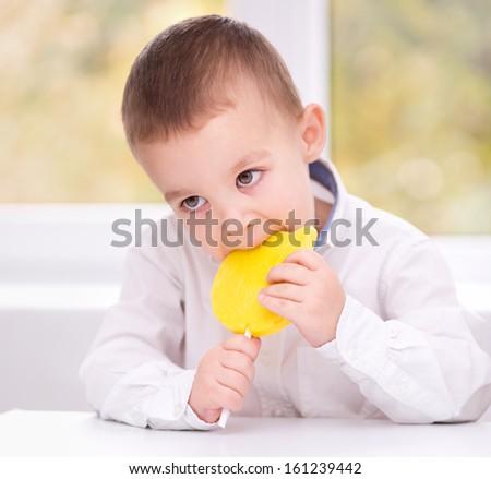 Happy little boy with big lollipop - stock photo
