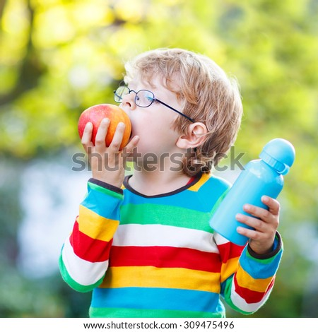 Happy little boy with books, apple and drink bottle on his first day to elementary school or nursery. Outdoors.  Back to school, kids, lifestyle concept. Child eating fruit - stock photo