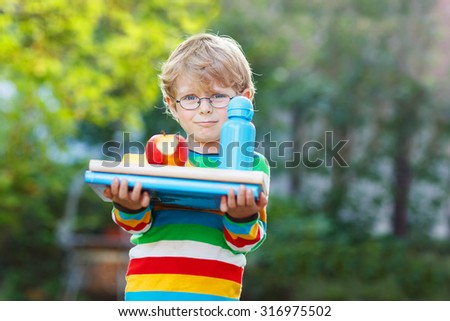 Happy little boy with books, apple and drink bottle on his first day to school or nursery. Outdoors.  Back to school, kids, lifestyle concept - stock photo