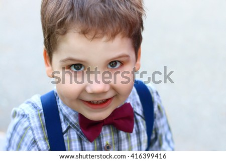 Happy little boy with bow tie smiles and looks at camera, top view - stock photo