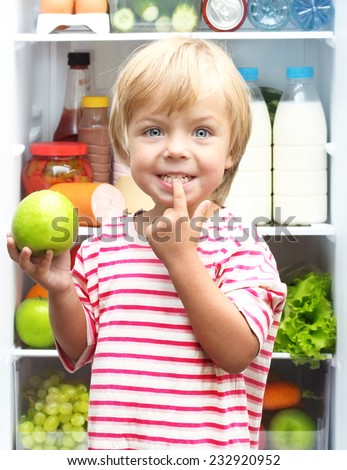 Happy little boy with green apple showing his teeth against refrigerator with food - stock photo