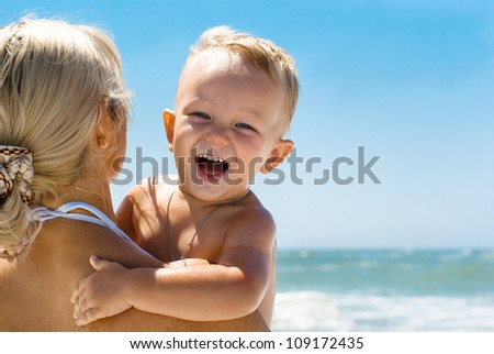 happy little boy with his mother on the beach with sea on background