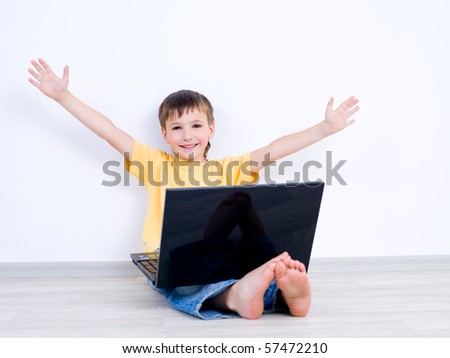 Happy little boy with laptop with moving apart his hands - indoors - stock photo