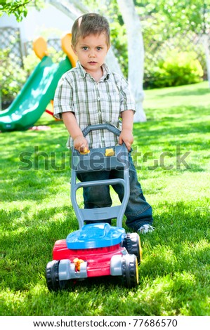Happy little boy with lawn mower in the garden - stock photo