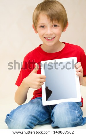 Happy little boy with tablet computer - stock photo