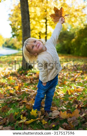 Happy little boy with yellow leaves in the beauty park