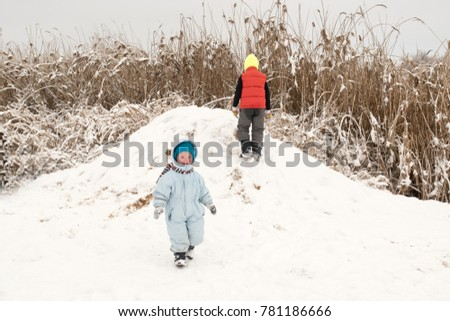 Happy little boys running around on a snow slide .. Active rest on a winter day. Casual boy's fashion