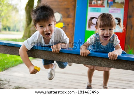 Happy little brother and his sister are playing in the playground - stock photo