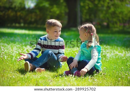 Happy little brother and sister playing on grass in park - stock photo