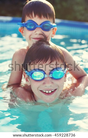 Happy little brothers in goggles swim, playing in pool, summer holiday