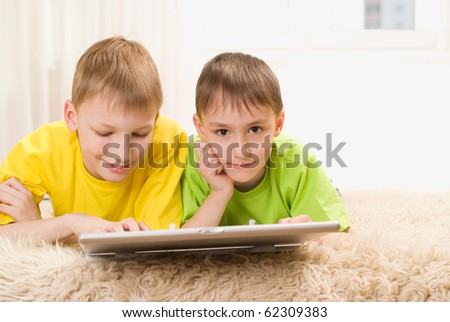happy little brothers lie with laptop
