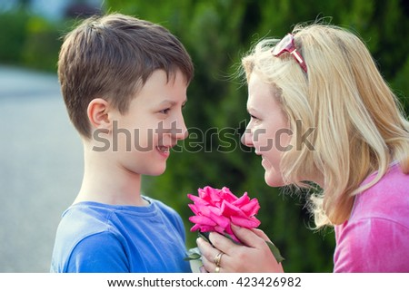 Happy little caucasian boy give flower to mom, mother's day, outdoor - stock photo