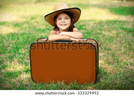 Happy little Caucasian girl in hat sitting behind suitcase, Outdoor portrait - stock photo