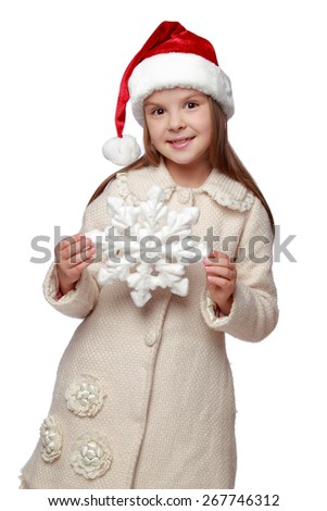 Happy little caucasian girl with long hair in red Santa hat holding white snowflake isolated on white/Studio Image cute child in a Santa hat with Christmas snowflake - stock photo