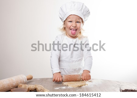 happy little chef unrolls dough and shows tongue - stock photo