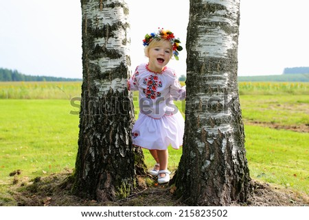Happy little child, adorable blonde girl dressed in national Ukrainian costume wearing wreath of flowers, peacefully playing in beautiful field in East of Ukraine - make love not war concept - stock photo