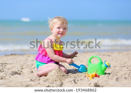 Happy little child, adorable blonde toddler girl in colorful swimsuit playing on the beach with toys building sand castle, North Sea, Belgium