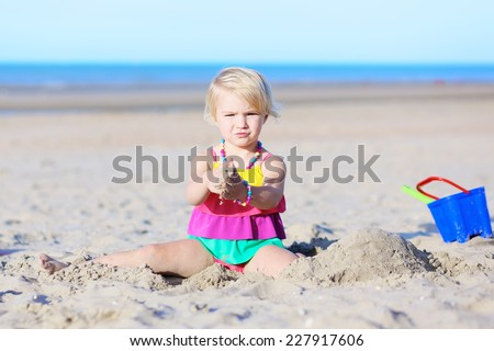 Happy little child, adorable blonde toddler girl wearing colorful necklace and swimsuit playing on the beach at North Sea - stock photo