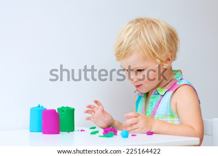 Happy little child, adorable toddler preschooler girl creating using play dough, colorful modeling compound - stock photo