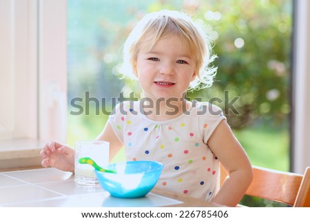 Happy little child, blonde curly toddler girl, enjoying healthy breakfast eating oatmeal porridge and drinking milk sitting in high chair at bright sunny kitchen next to big garden view window - stock photo