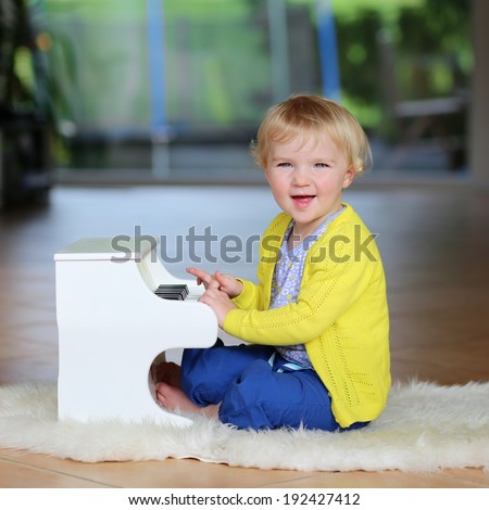 Happy little child, blonde curly toddler girl having fun playing piano toy sitting on the sheepskin lying on the tiles floor in big room with garden view window - stock photo