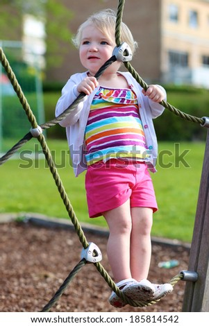 Happy little child, blonde toddler girl in colorful casual suit, having fun on the playground climbing on the net on a sunny summer day - stock photo