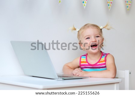 Happy little child, blonde toddler girl, playing with laptop at home or school - early development and education concept - stock photo