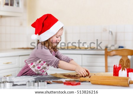 Happy little child, cute kid girl, sitting at the table in domestic kitchen making delicious sweet gingerbread xmas cookies. Kitchen decorated for Christmas holiday. Girl helping  with baking.
