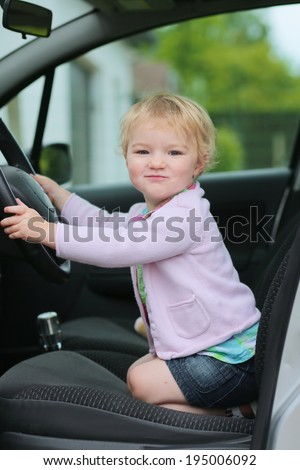 Happy little child, funny blonde toddler girl sitting on her knees inside of the car on driver seat holding steering wheel