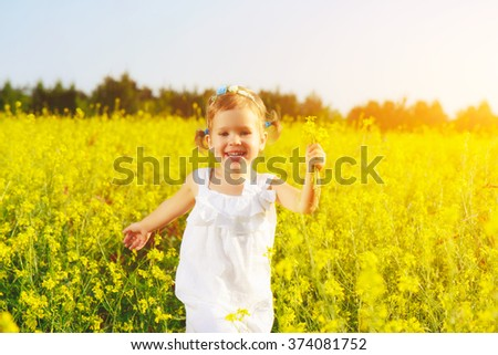happy little child girl in a white dress running on field with a bouquet of yellow flowers - stock photo