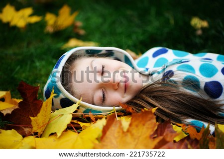 Happy little child girl lying on the grass and yellow maple leaves in autumn park - stock photo