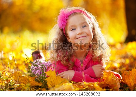 Happy little child in autumn park - stock photo