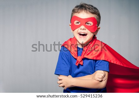 Happy little child playing superhero. Kid having fun outdoors. Concept of boy power.