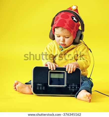 Happy little child wearing headphones - stock photo