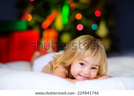 happy little child with gifts and Christmas tree and lights - stock photo