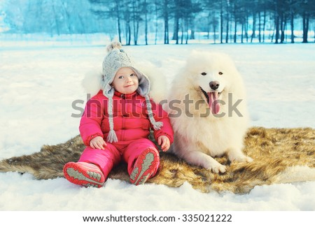 Happy little child with white Samoyed dog sitting on snow in winter day - stock photo