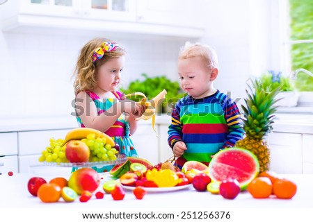 Happy little children, cute toddler girl and funny baby boy, brother and sister, eating fresh ripe fruit for healthy breakfast in a white sunny family kitchen with window - stock photo
